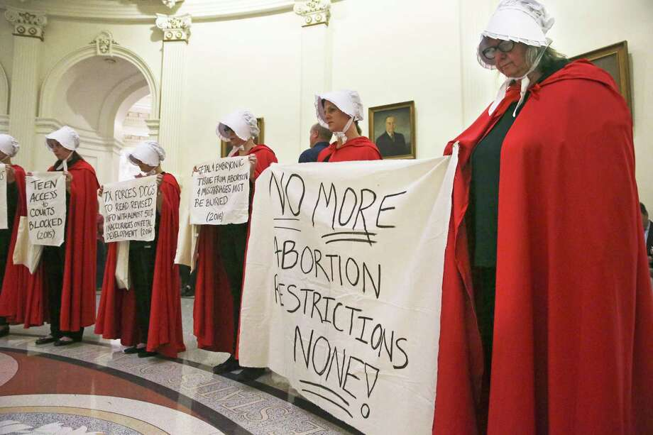 Women dressed in clothing from The Handmaid's Tale stand in silence as abortion rights protestors gather in the Capitol rotunda to protest legislation restricting abortion procedures which eventually passed. A judge in Austin heard testimony in a hearing Tuesday morning seeking to stop a law prohibiting a common second-trimester abortion procedure from taking effect Sept. 1. Photo: Tom Reel /San Antonio Express-News / 2017 SAN ANTONIO EXPRESS-NEWS