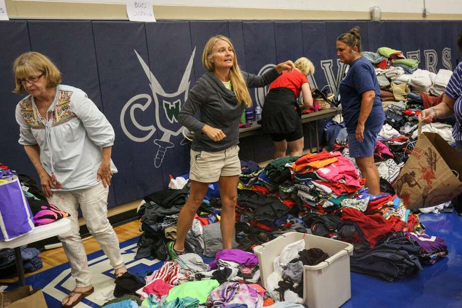 The Woodlands resident Mary O'Neil-Kob helps organize clothing donations and volunteers Monday at the College Park High School shelter in The Woodlands. Many business with a presence in Texas have announced major donations and fund drives. Photo: Michael Minasi /Houston Chronicle / Internal
