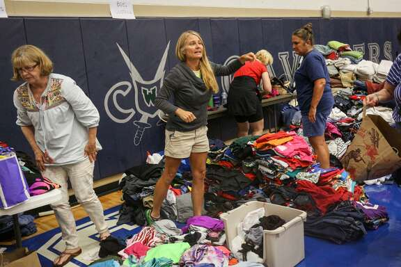 The Woodlands resident Mary O'Neil-Kob helps organize clothing donations and volunteers Monday at the College Park High School shelter in The Woodlands. Many business with a presence in Texas have announced major donations and fund drives.