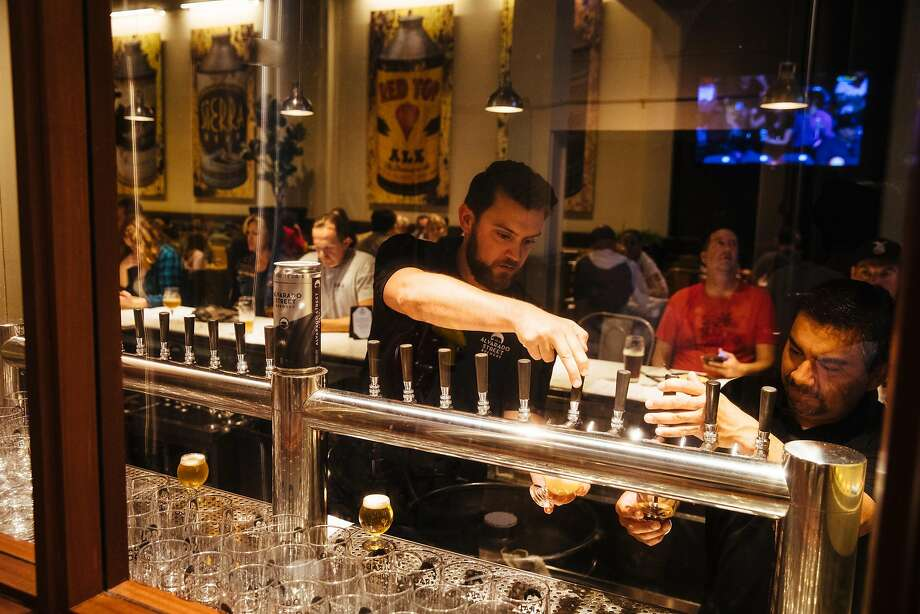 Bartenders James Wall (left) and Federico Cardenas serve up the beer at the Alvarado Street Brewery in Monterey. Photo: Mason Trinca, Special To The Chronicle