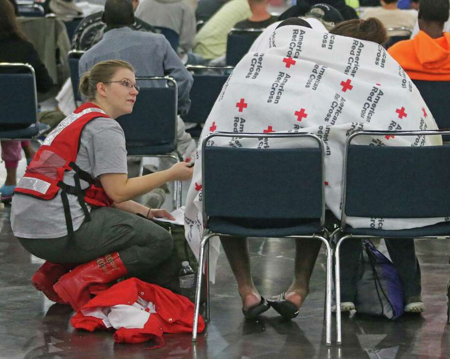 American Red Cross worker Katrina Dirscherl talks with Oralia Guerra and Diamond Robinson as they huddle together to stay warm underneath Red Cross blankets at Houston's George Brown Convention Center on Monday. The American Red Cross is an accredited charity by the Better Business Bureau, which warns that some appeals for charitable donations are scams. Photo: Louis DeLuca /TNS / Dallas Morning News