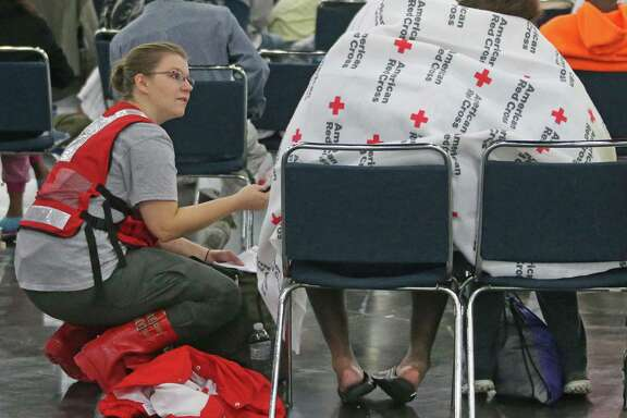 American Red Cross worker Katrina Dirscherl talks with Oralia Guerra and Diamond Robinson as they huddle together to stay warm underneath Red Cross blankets at Houston's George Brown Convention Center on Monday. The American Red Cross is an accredited charity by the Better Business Bureau, which warns that some appeals for charitable donations are scams.