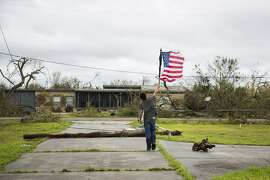 CORRECTS DAY TO SUNDAY FROM SATURDAY - In this Sunday, Aug. 27, 2017 photo, Layton Carpenter walks down an empty driveway in Bayside, Texas, holding a broken American flag that he found in the water after Hurricane Harvey hit Bayside, Texas. (Olivia Vanni/The Victoria Advocate via AP)