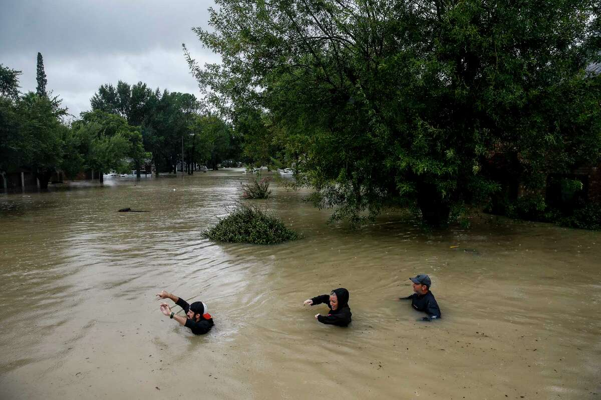 People wade through chest deep water down Pine Cliff Drive as Addicks Reservoir nears capacity due to near constant rain from Tropical Storm Harvey Tuesday, Aug. 29, 2017 in Houston.