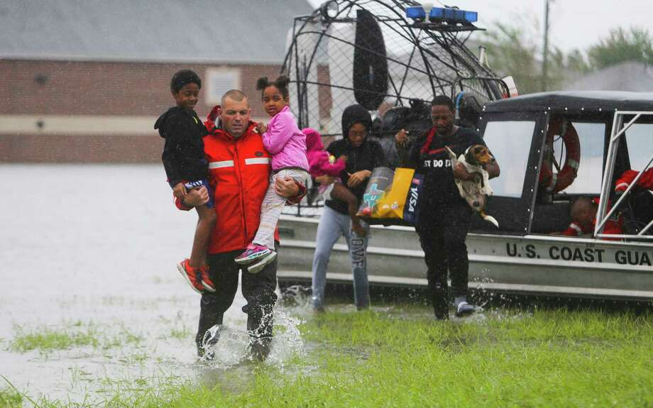 Seven-year-old Elijah and 4-year-old Jordan Rylander are brought assure by the U.S. Coast Guard along with their parents, Perry and Keri, and sister Zoey, 2, near the HEB on Blackhawk Blvd. at the south Sam Houston Tollway, Tuesday, Aug. 29, 2017, in Houston. Photo: Mark Mulligan, Houston Chronicle / 2017 Mark Mulligan / Houston Chronicle