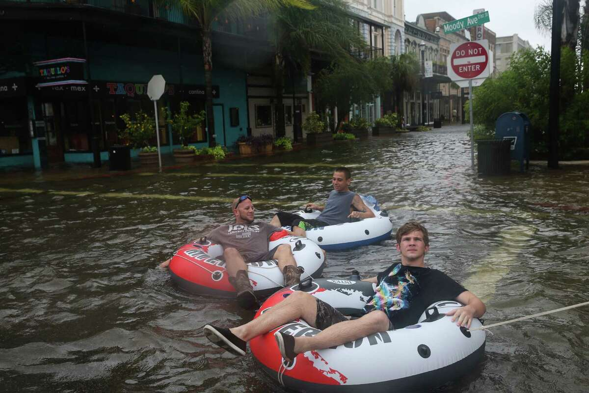 Grant Braswell, from front, Shayne Hofstetter and John Hall have a good time tubing in flood water at the intersection of Moody Avenue and Postofdice Street on Tuesday, August 29, 2017, in Galveston. Some parts of the downtown section had flood water more than waist-deep.