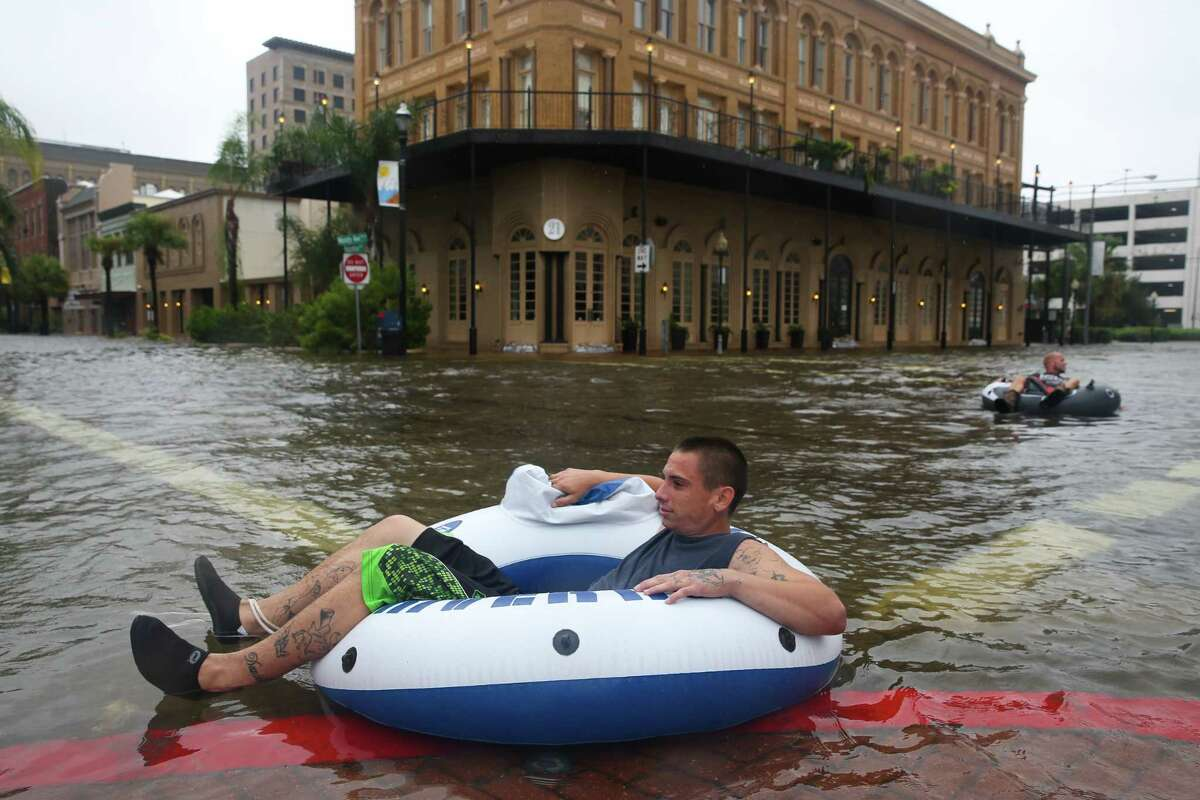 John Hall and his brother Shayne Hofstetter have a good time tubing with friends in flood water at the intersection of Moody Avenue and Postofdice Street on Tuesday, August 29, 2017, in Galveston. Some parts of the downtown section had flood water more than waist-deep.