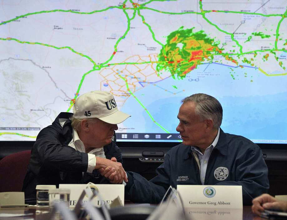 CORRECTION - President Donald Trump shakes hands with Texas Governor Greg Abbott at the Texas Department of Public Safety Emergency Operations Center in Austin, Texas on August 29, 2017, as rains from Hurricane Harvey continue to flood parts of Texas. US President Donald Trump flew into storm-ravaged Texas Tuesday in a show of solidarity and leadership in the face of the deadly devastation wrought by Harvey -- as the battered US Gulf Coast braces for even more torrential rain.   / AFP PHOTO / JIM WATSON / The erroneous mention appearing in the metadata of this photo by JIM WATSON has been modified in AFP systems in the following manner: [Austin, Texas] instead of [Corpus Christi, Texas]. Please immediately remove the erroneous mention[s] from all your online services and delete it from your servers. If you have been authorized by AFP to distribute it to third parties, please ensure that the same actions are carried out by them. Failure to promptly comply with these instructions will entail liability on your part for any continued or post notification usage. Therefore we thank you very much for all your attention and prompt action. We are sorry for the inconvenience this notification may cause and remain at your disposal for any further information you may require.JIM WATSON/AFP/Getty Images Photo: JIM WATSON, Contributor / AFP/Getty Images / AFP or licensors