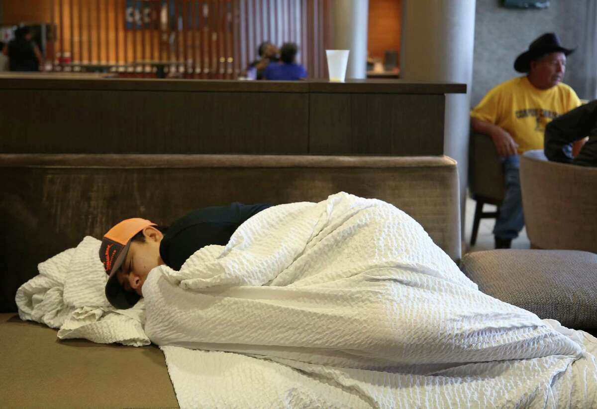 Cilla Padron, from Corpus Christi, takes a nap in the lobby of the SpringHill Suites hotel Tuesday, Aug. 29, 2017, in Rosenberg, Texas. Padron and her friends worked most of the previous day helping rescue people from flooded neighborhoods.