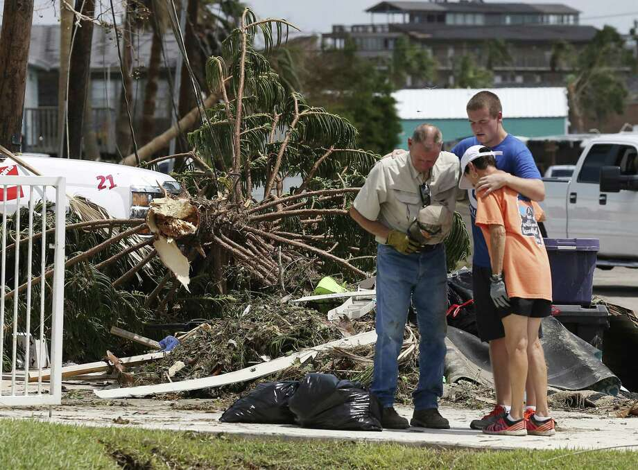 Avery Bell, 19, with Church Unlimited, prays with Elroy Jonas, 71, and his wife, Jeanne, 66, in front of their home in Port Aransas, Texas, Tuesday, August 29, 2017. The couple is from New Braunfels and their home in Port Aransas flooded due to the surge from Hurricane Harvey last Friday. Photo: JERRY LARA / San Antonio Express-News / San Antonio Express-News