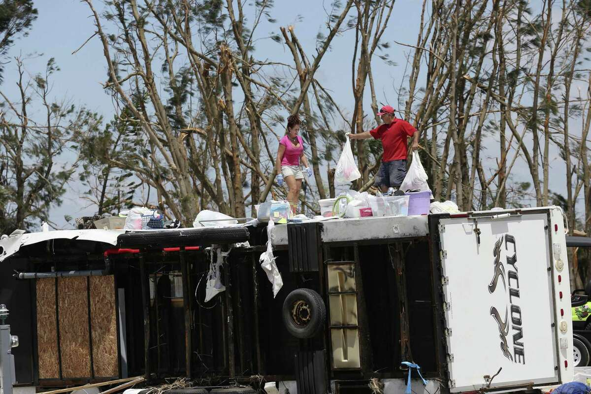 Glen Gonzales, 47, helps Brenda Travieso, 53, both from San Antonio, remove personal belongings from a travel trailer in the Tropic Island Resort in Port Aransas, Texas, Tuesday, August 29, 2017. The trailer and many others in the area were damaged by the surge and wind from Hurricane Harvey last Friday night.