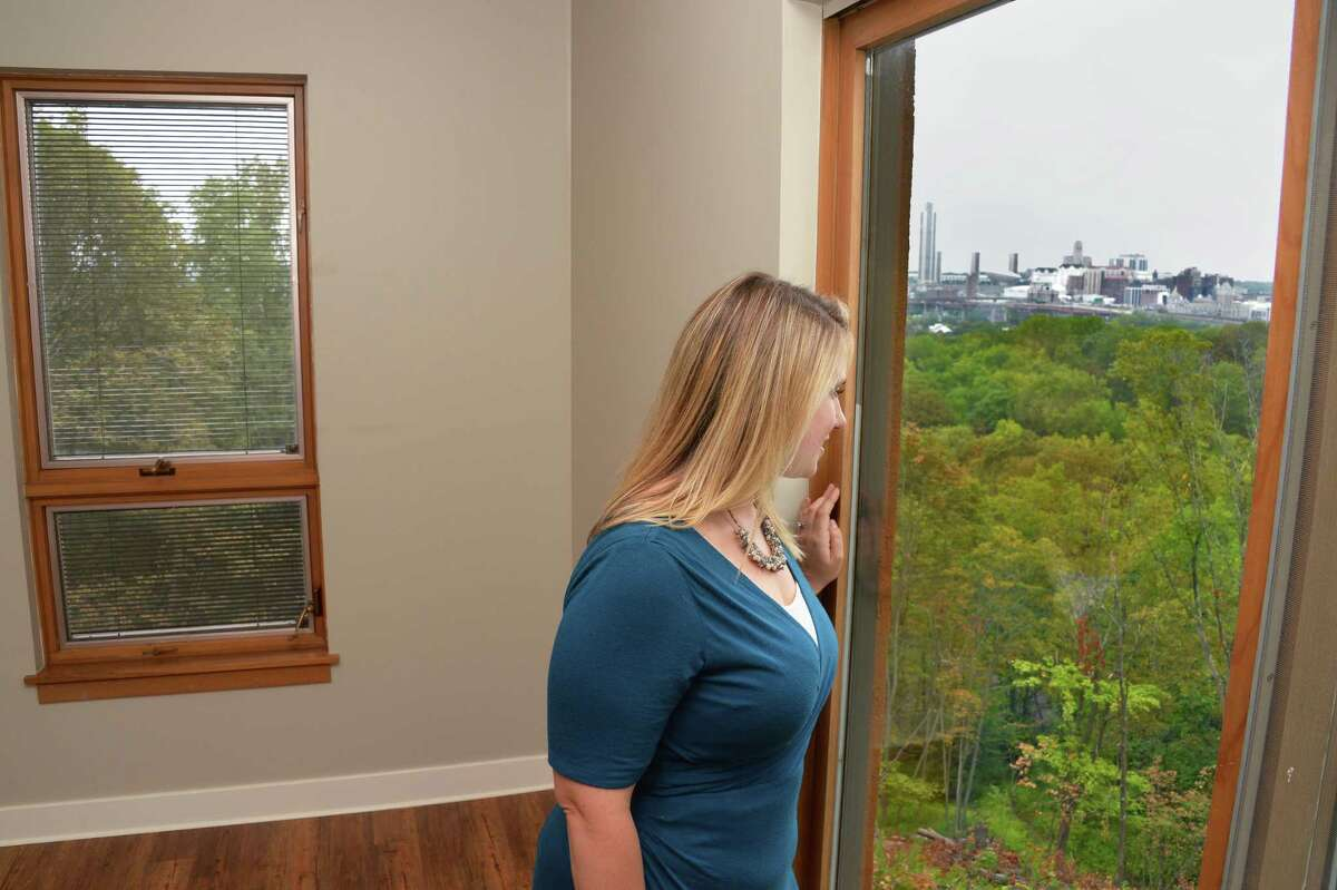 Renssealer County Chamber of Commerce's Staci O'Neill checks out the view of the Albany skyline during a tour of the new luxury Falls Edge Apartments on High Street Tuesday August 29, 2917 in Rennselaer, NY. (John Carl D'Annibale / Times Union)
