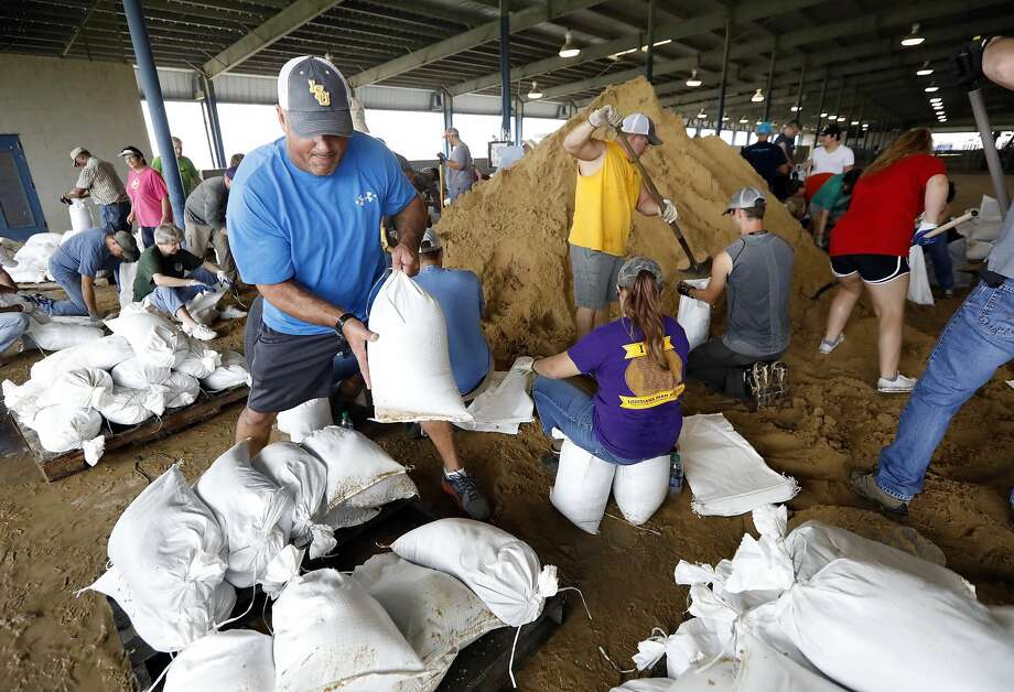 A volunteer loads sand bags on a pallet as others fill them for resident distribution at the Burton Coliseum in Lake Charles. Photo: Rogelio V. Solis, Associated Press