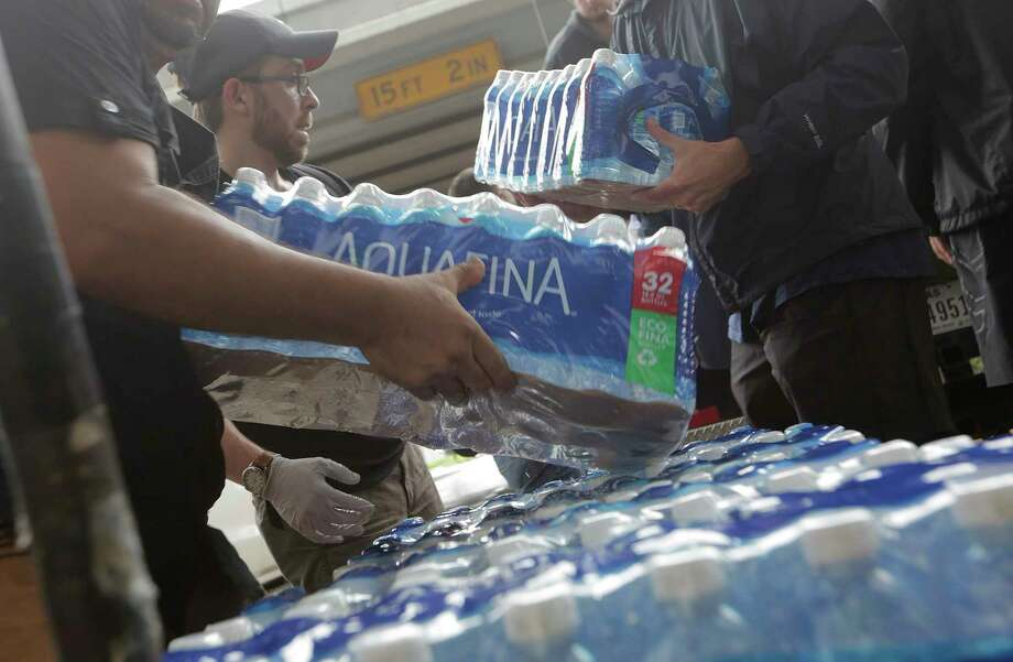 Volunteers unload donated bottled water at George R. Brown Convention Center in  Houston as Tropical Storm Harvey inches its way through the area on  Tuesday, Aug. 29, 2017.See more images from the historic storm. Photo: Elizabeth Conley, Houston Chronicle / © 2017 Houston Chronicle