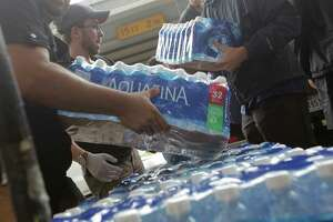 Volunteers unload donated bottled water at George R. Brown Convention Center in  Houston as Tropical Storm Harvey inches its way through the area on  Tuesday, Aug. 29, 2017.