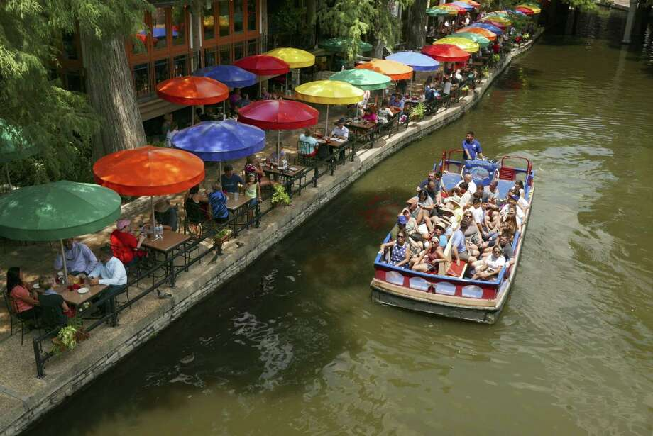 A river barge makes its way by Casa Rio along the River Walk on Aug. 4. It first opened its doors in 1946. With its colorful umbrellas, it is among the most popular and iconic restaurants on the River Walk. Photo: Billy Calzada /San Antonio Express-News / San Antonio Express-News