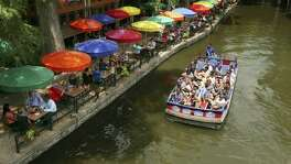 A river barge makes its way by Casa Rio along the River Walk on Aug. 4. It first opened its doors in 1946. With its colorful umbrellas, it is among the most popular and iconic restaurants on the River Walk.