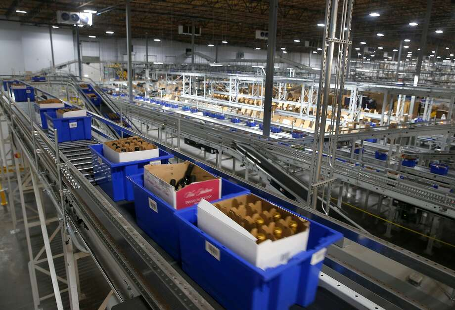 Blue bins containing cases of wine are transported by a network of conveyors for order fulfillment or restocking in the WineDirect warehouse in American Canyon. The new center ships tens of thousands of bottles of wine per day. Photo: Paul Chinn, The Chronicle
