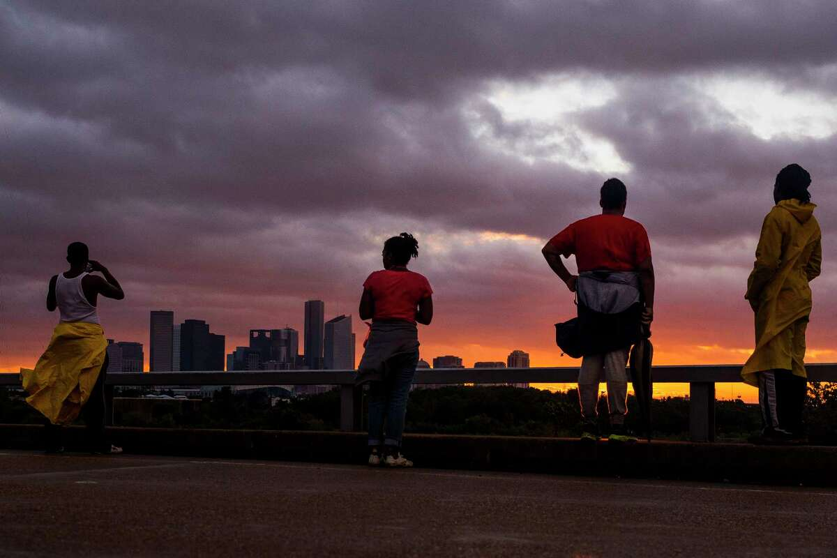 People stand on Hirsch Road to watch the sun sets over the Houston skyline as Tropical Storm Harvey moves out of the region Tuesday, Aug. 29, 2017.