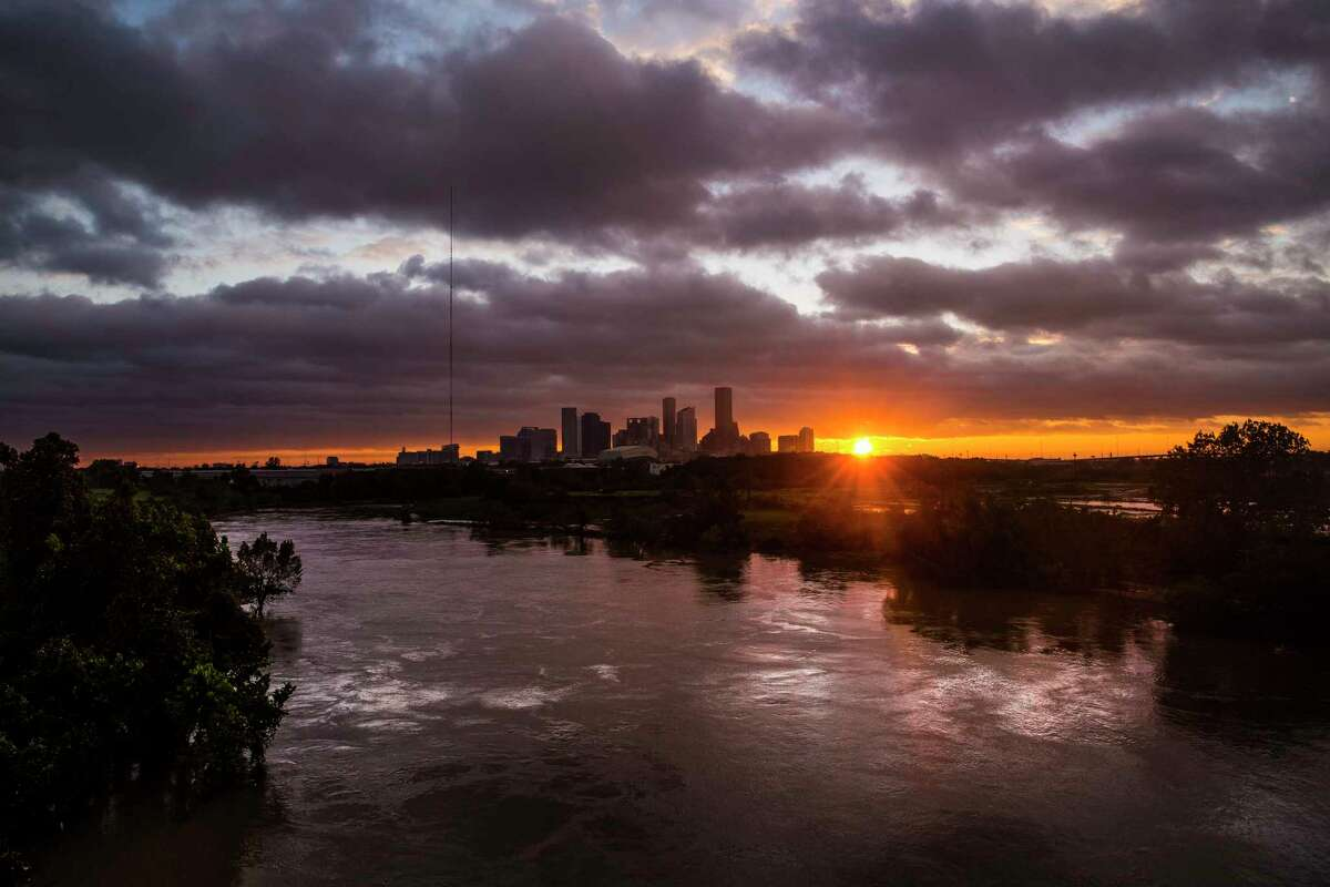 The sun sets over the Houston skyline as Tropical Storm Harvey moves out of the region Tuesday, Aug. 29, 2017.