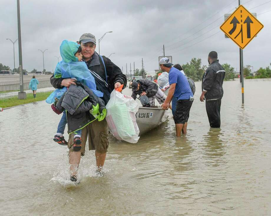 Volunteers and first responders work together to rescue residents from rising flood waters in Houston. (Scott Clause/The Daily Advertiser via AP) Photo: Scott Clause, MBR / Scott Clause/The Advertiser