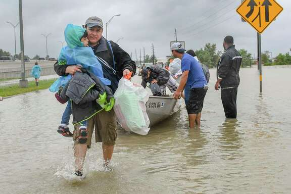Volunteers and first responders work together to rescue residents from rising flood waters in Houston. (Scott Clause/The Daily Advertiser via AP)