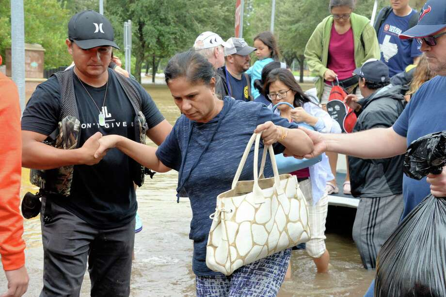Residents of the Cinco Ranch and Canyon Gate subdivisions of Ft. Bend County are helped off of a boat after evacuating from their homes that sit near the west side of the Barker Reservoir along South Mason Road in Katy, TX on August 29, 2017. Photo: Craig Moseley, Staff / ©2017 Houston Chronicle