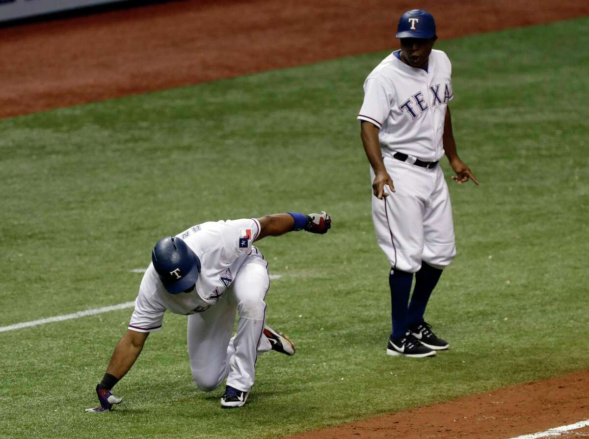 Texas Rangers' Elvis Andrus falls down after hitting a triple off Houston Astros relief pitcher Francis Martes during the fifth inning of a baseball game Tuesday, Aug. 29, 2017, in St. Petersburg, Fla. The Astros moved their three-game home series against the Rangers to St. Petersburg because of unsafe conditions from Hurricane Harvey. (AP Photo/Chris O'Meara)