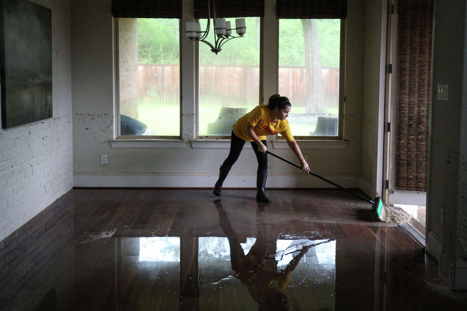 Woodforest resident Katie Marshall pushes water from the flooded home of fellow Woodforest resident Thomas Cox on Tuesday, Aug. 29, 2017. (Michael Minasi / Chronicle) Photo: Michael Minasi, Staff Photographer / © 2017 Houston Chronicle