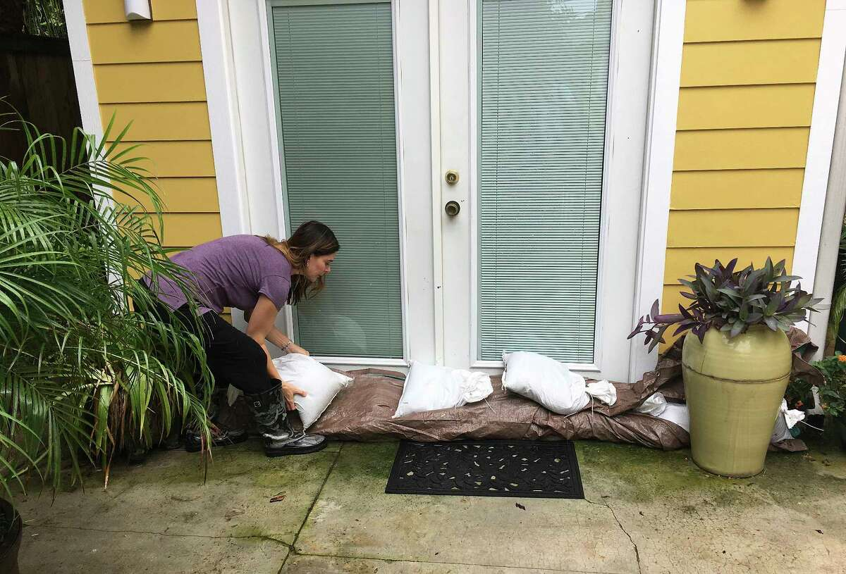 Nancy Gunn adjusts sandbags at a doorway into the Auld Sweet Olive Bed and Breakfast in New Orleans on Tuesday, Aug. 29, 2017. Gunn, the owner, says part a ground floor room took on water during an early August flash flood and she was hoping to avoid the same fate as bands of rain from Tropical Storm Harvey moved over the city. (AP Photo/Kevin McGill)
