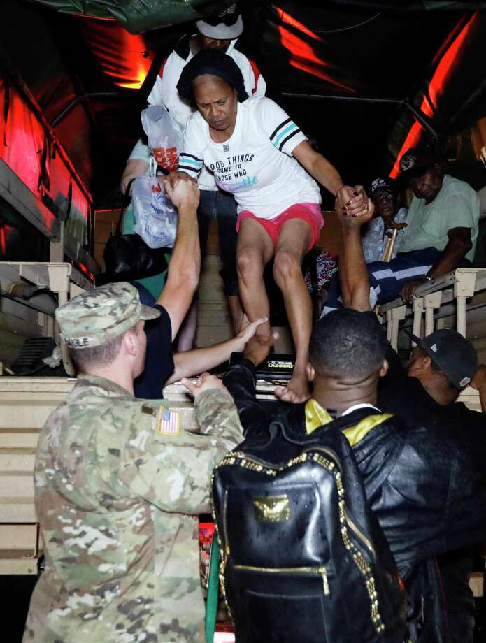Lake Charles rescue personnel help residents exit from the back of a vehicle late Monday night, Aug. 28, 2017, in Lake Charles, La., after flooding from Harvey's almost constant rain over the last two days overcame the city's drainage system, flooding several subdivisions and necessitating home rescues. (AP Photo/Rogelio V. Solis) Photo: Rogelio V. Solis, STF / Copyright 2017 The Associated Press. All rights reserved.