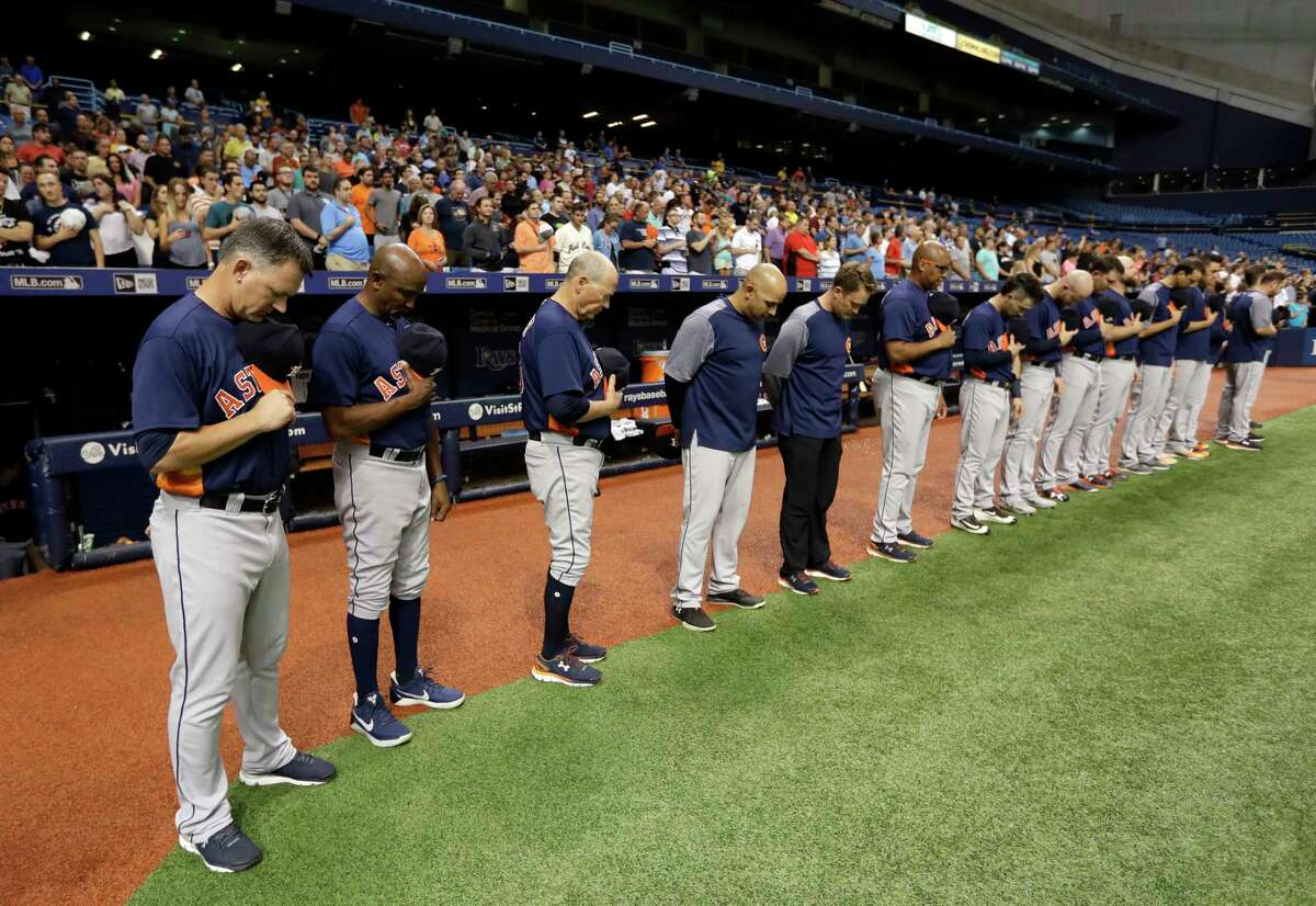 Members of the Astros, including manager A.J. Hinch, left, observe a moment of silence for Harvey victims before Tuesday night's game at Tropicana Field.