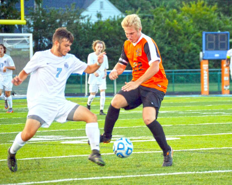 Edwardsville senior forward Alec Mills, right, battles for a loose ball at midfield with a Belleville East defender during first-half action on Tuesday in Belleville.