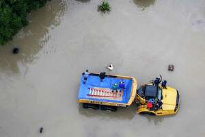 Flood victims are evacuated on a large truck in a neighborhood flooded by Tropical Storm Harvey on Tuesday, Aug. 29, 2017, in Houston.