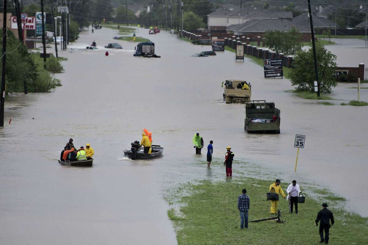 Volunteer rescuers evacuate people from a flooded residential area during the aftermath of Hurricane Harvey on August 29, 2017 in Houston, Texas. Floodwaters have breached a levee south of the city of Houston, officials said Tuesday, urging residents to leave the area immediately. / AFP PHOTO / Brendan SmialowskiBRENDAN SMIALOWSKI/AFP/Getty Images