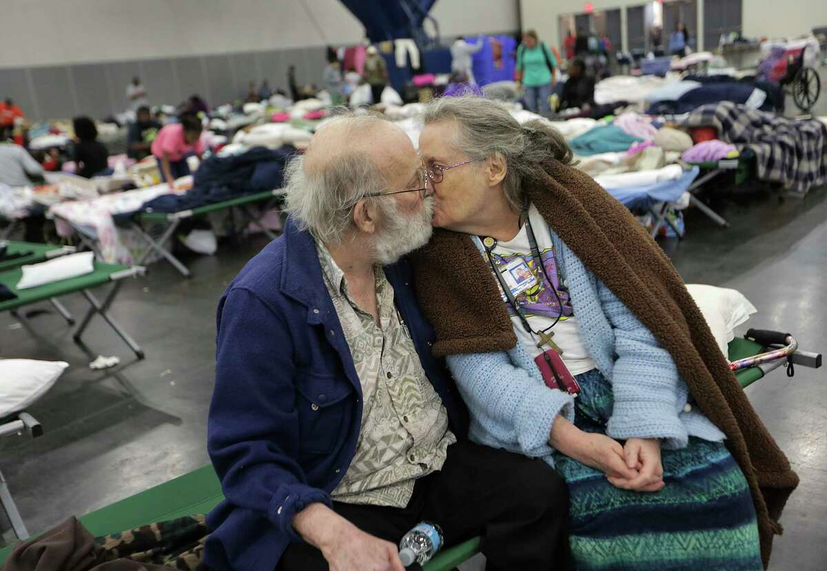 Ron and Peg Sauter kiss as they take refuge from Hurricane Harvey at the George R. Brown Convention Center on Tuesday. The couple celebrated their 55th wedding anniversary on Aug. 22. They were among 10,000 evacuees at the shelter.