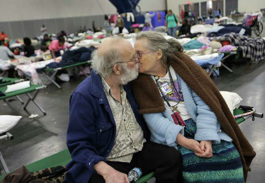 Ron and Peg Sauter kiss as they take refuge from Hurricane Harvey at the George R. Brown Convention Center on Tuesday.  The couple celebrated their 55th wedding anniversary on Aug. 22. They were among 10,000 evacuees at the shelter. Photo: Elizabeth Conley, Houston Chronicle / © 2017 Houston Chronicle