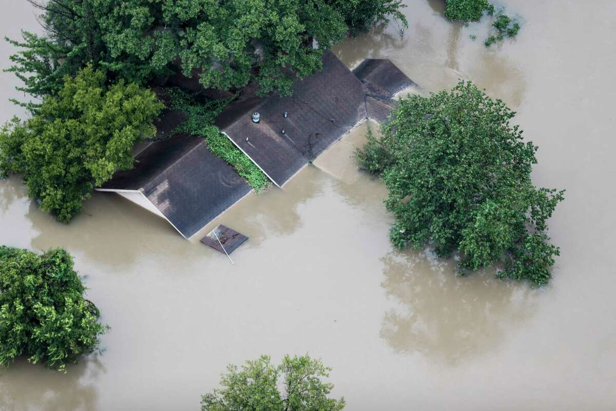 A flooded out house is shown with waters from Tropical Storm Harvey up to its rooftops on Tuesday, Aug. 29, 2017, in Houston.