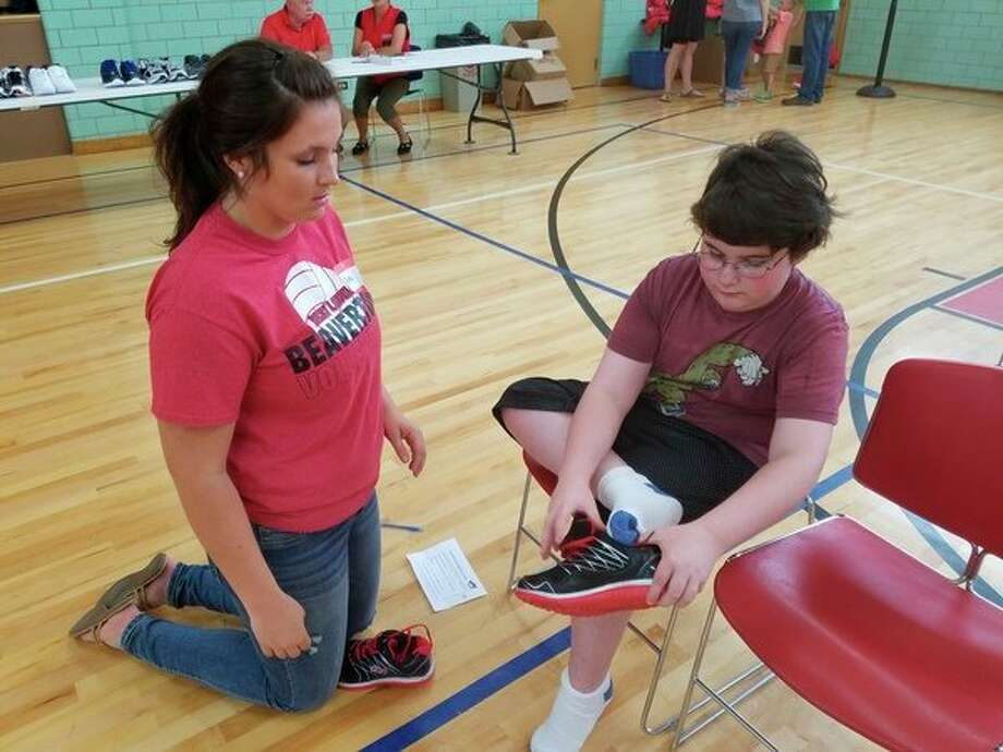 Volunteer Amaya Ware, left, helps Austin Dobson find the right shoe.(Tereasa Nims/for the Daily News)