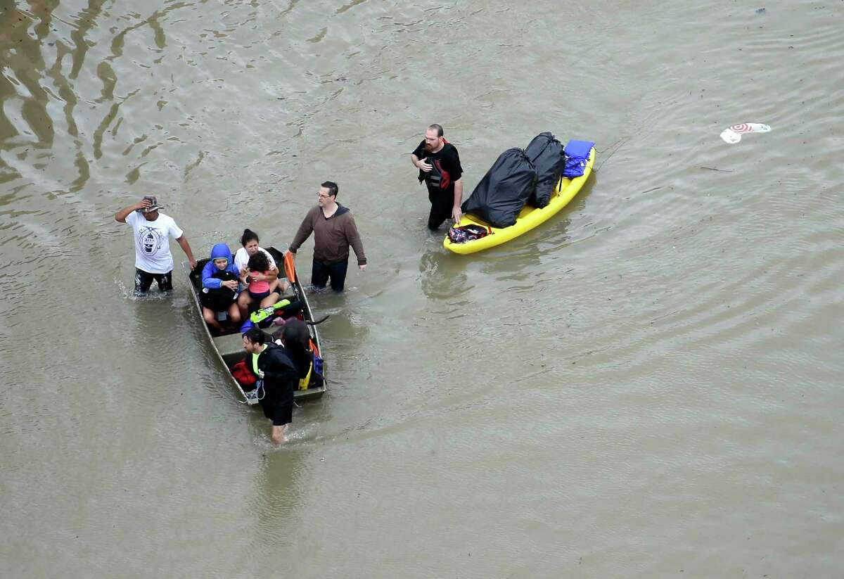 Residents wade through floodwaters as they evacuate their homes near the Addicks Reservoir as floodwaters from Tropical Storm Harvey rise Tuesday, Aug. 29, 2017, in Houston. (AP Photo/David J. Phillip) ORG XMIT: TXDP133