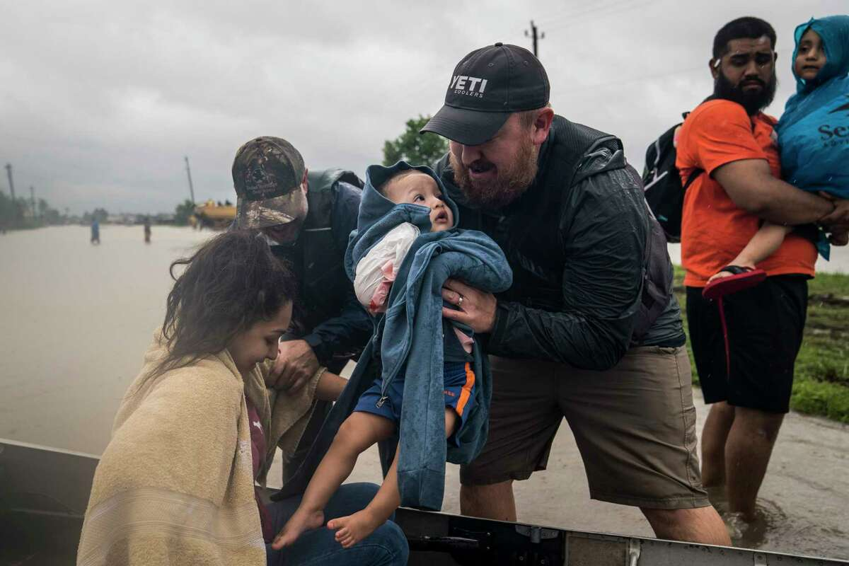 Glenda Montelongeo, Richard Martinez and his two sons are helped out of a boat after being rescued Tuesday near Tidwell Road and Toll Road 8 in Houston.