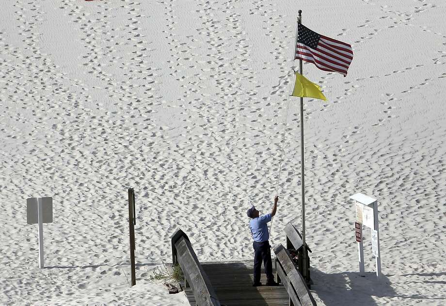 A worker at the Phoenix VI condominium complex raises the American flag along with a yellow flag indicating medium hazard in the Gulf of Mexico waters off Orange Beach, Ala., on Monday. Photo: Jacqueline Larma, Associated Press