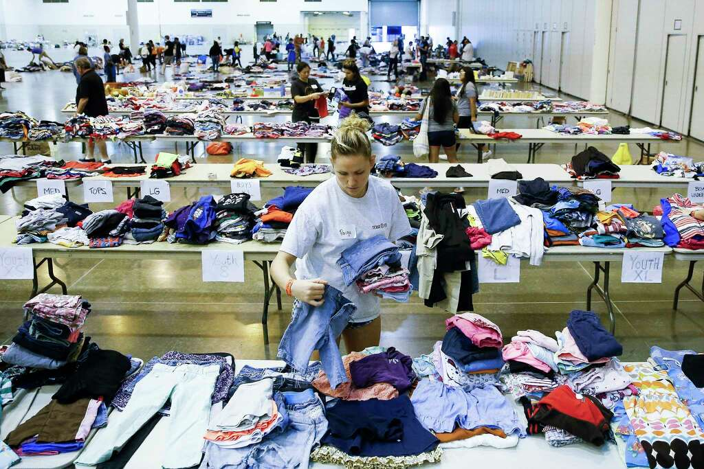 Volunteer Paige Atkinson sorts donated clothing at NRG Center, which opened its doors to a