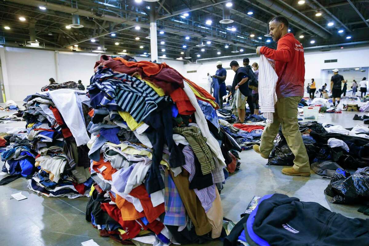 Volunteer Gene Donahue helps sort donated clothing at NRG Center, which opened its doors to a capacity of 10,000 evacuees in the wake of Tropical Storm Harvey Wednesday, Aug. 30, 2017 in Houston.
