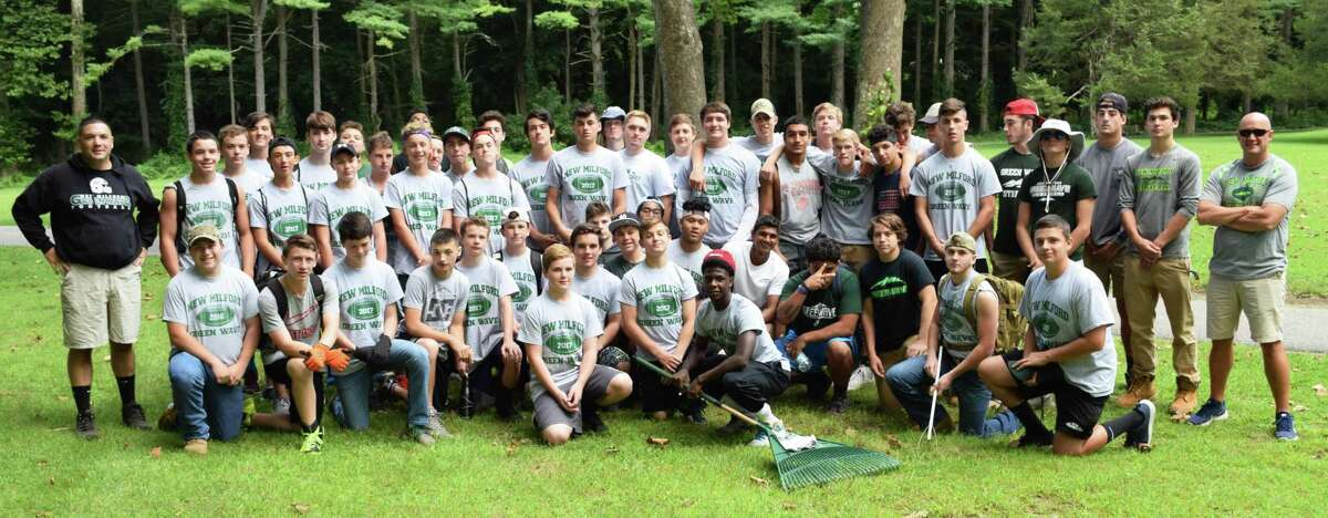 About 60 members of the New Milford High School football team, led by Coach Larry Badaracco, left, and Assistant Coach Chuck Lynch, participated in a community cleanup project at Harrybrooke Park & Harden House Museum Aug. 25.