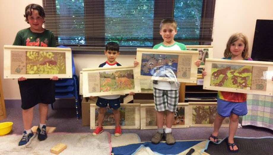 Gunn Memorial Junior Library in Washington recently celebrated the launch of a StoryWalk. Above, children, from left to right, Jake Gervasio, Drew Campelli, and David and Sarah Low, all from Washington, proudly display the board they assembled at a recent woodworking event. Photo: Courtesy Of Gunn Memorial Library / The News-Times Contributed