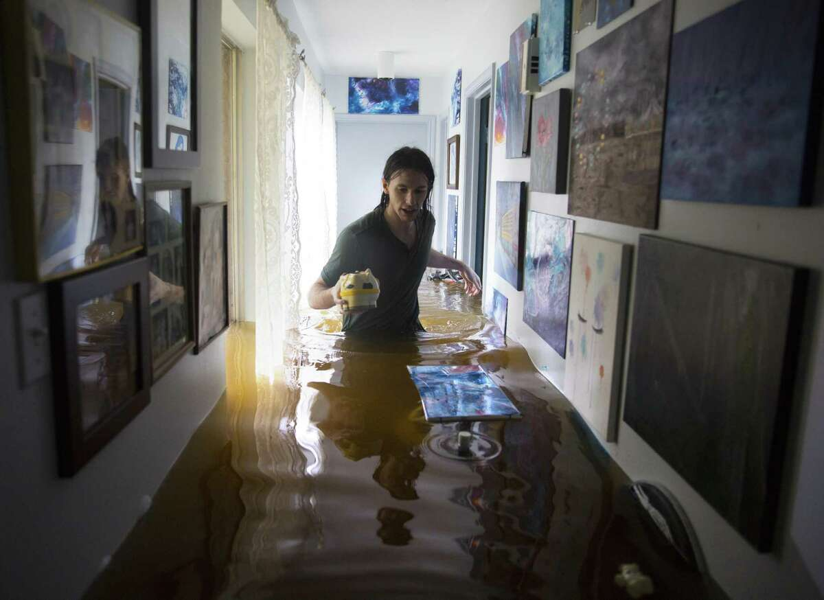 Matthew Koser wades through his grandfather's house in West Houston after it was flooded by heavy rains from Harvey. Owners of flooded houses and businesses will have to deal with a lack of skilled construction workers at a time they need help the most.