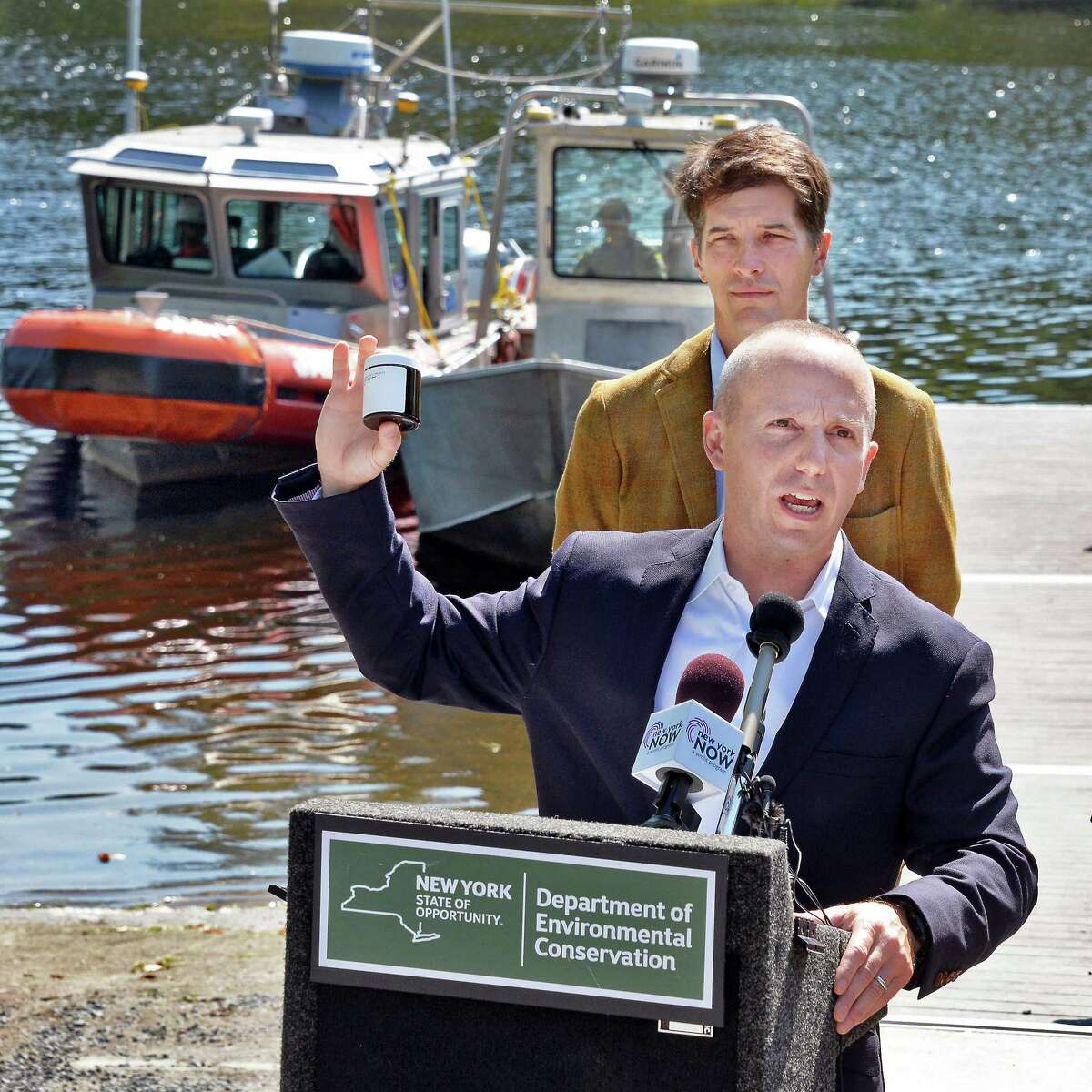 DEC Commissioner Basil Seggos holds up one of 1,600 samples collected from the upper Hudson River during a news conference calling for continued PCB clean-up in the river Wednesday August 30, 2017 in Moreau, NY. Scenic Hudson's Andy Bicking at top. (John Carl D'Annibale / Times Union)