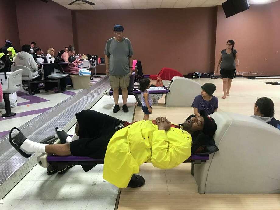 A man sleeps on a bowling ball return inside Max Bowl.Photo: Kim Brent Photo: BE