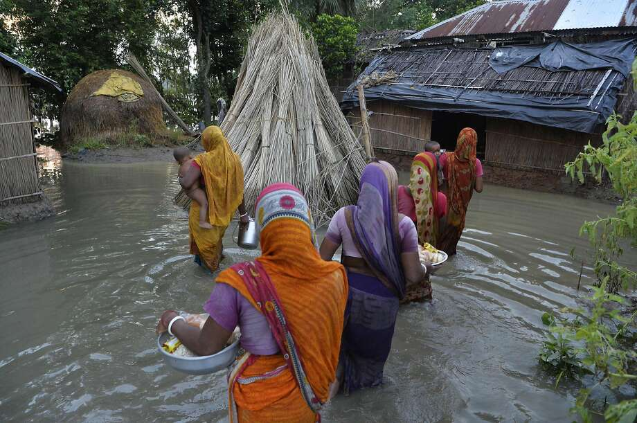 TOPSHOT - Indian villagers wade through flood waters after collecting relief food near the submerged houses in Gazole village at Malda district in the Indian state of West Bengal on August 22, 2017.  More than 24 million people have been affected by some of the worst flooding to hit South Asia in decades, with large areas of land submerged in water. Authorities in Bangladesh, India and Nepal have put the death toll at more than 750 since August 10, when a series of deluges began spreading with the annual monsoon season.  / AFP PHOTO / DIPTENDU DUTTADIPTENDU DUTTA/AFP/Getty Images Photo: DIPTENDU DUTTA, AFP/Getty Images